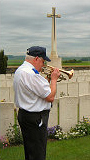 """Grainger Rock plays """"The Last Post"""" at the grave of Lt. J. Hitchon at Queens Cemetry"""